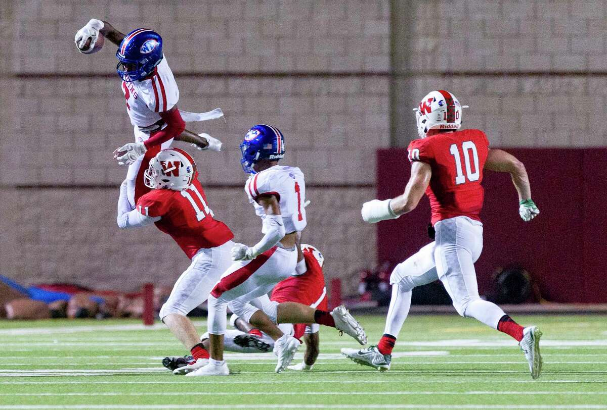 The Woodlands linebacker Dylan Calvetti (11) tackles Beaumont West Brook quarterback La'Ravien Elia (3) in midair during the first quarter of a District 12-6A high school football game at Woodforest Bank Stadium on Thursday, Oct. 12, 2017, in Shenandoah.