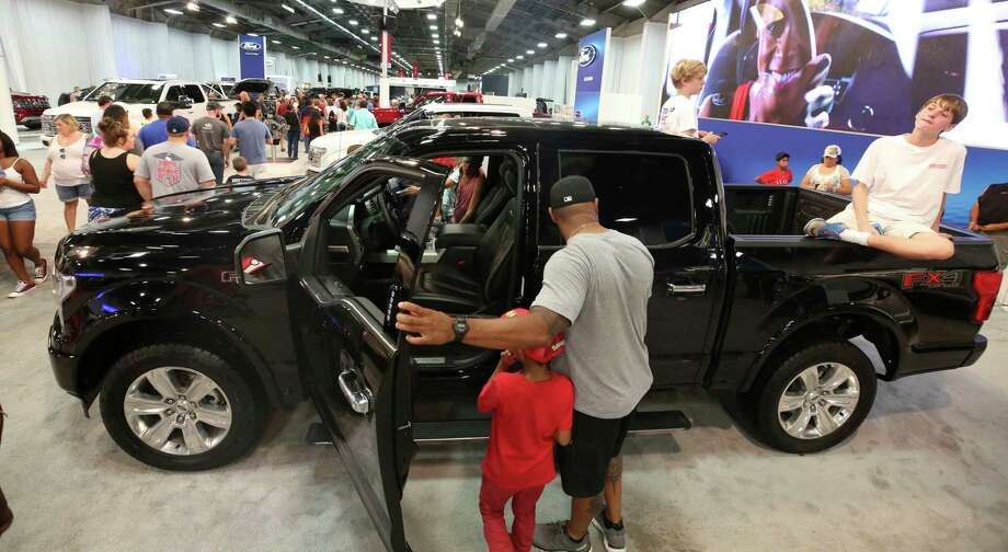 In this Monday, Oct. 9, 2017, photo, fairgoers look at pickup trucks on display at the State Fair of Texas in Dallas. America's favorite luxury vehicle is a pickup truck. Buyers are increasingly outfitting their pickups with all the comforts of luxury cars, from heated and cooled seats to backup cameras to panoramic glass roofs. (AP Photo/LM Otero) Photo: LM Otero, STF / Copyright 2017 The Associated Press. All rights reserved.