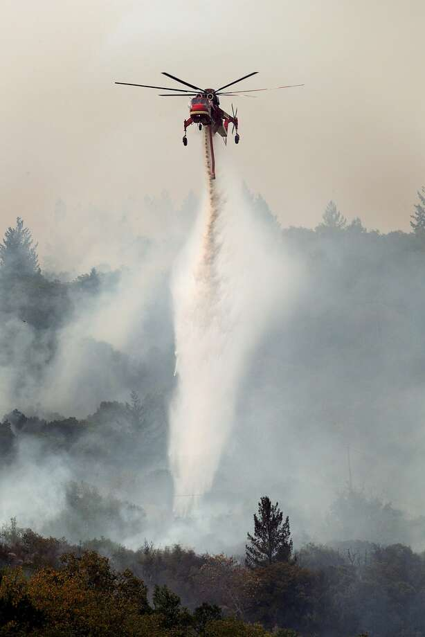 A Cal Fire helicopter drops water on a smoldering area as the Partrick Fire continue to burn east of Sonoma, Calif., on Thursday, October 12, 2017. The Napa and Sonoma valleys continued to be under threat from several fires not yet under control amid growing fears that strong winds might worsen the situation. Photo: Carlos Avila Gonzalez, The Chronicle