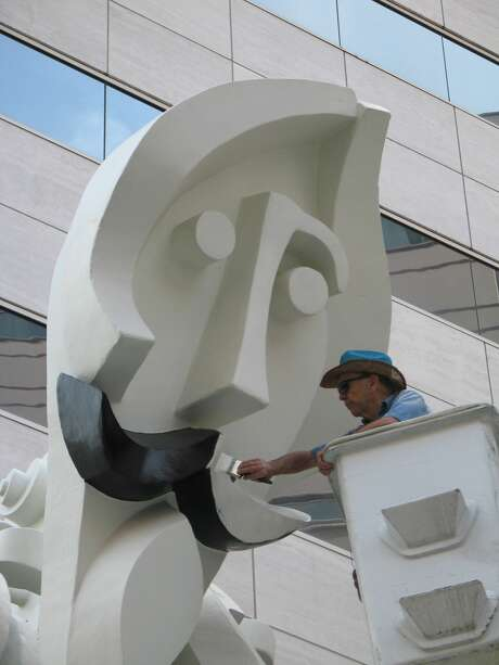 In 2005, Adickes had to apply a new coat of white paint on the mustache of his statue after the office building's property management group ordered the mustache painted black. They later provided the bucket truck and paint after Adickes and others in the arts community said it overstepped its bounds in altering the artwork. Photo: Larry Reese/HOUSTON CHRONICLE