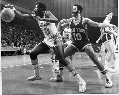 Baltimore Bullets' guard Earl Monroe scrambles after the ball while guarded by New York Knicks' Walt Frazier in the first quarter of the NBA's Eastern Division semi-final playoff in Baltimore, Md., April 5, 1970.  New York's Bill Bradley watches in background.  (AP Photo/Bob Schutz)
