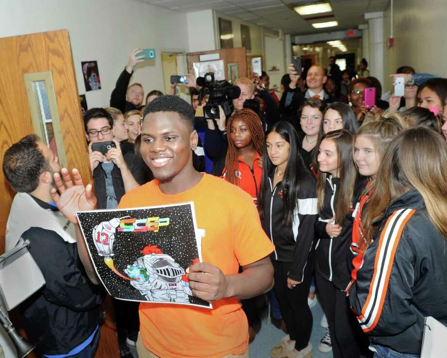Surprise celebration at Stamford High School, Conn., Friday, Oct. 13, 2017, to honor Stamford High School senior Krantz Medeus, 17, at center waving holding the NASA patch that he designed that was selected as a district-wide contest winner that will be sent to the Johnson Space Center and flown into space to be used affixed to astronauts uniforms. Photo: Bob Luckey Jr. / Hearst Connecticut Media / Greenwich Time