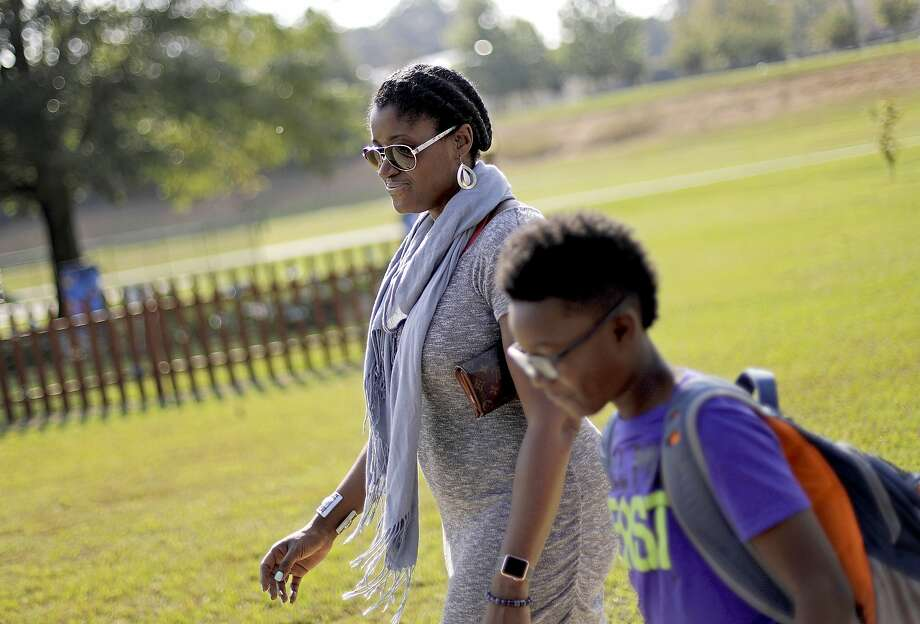 "Corrie Davis (left) picks up her son, Turner, from school in Kennesaw, Ga. A white student, dressed as a plantation owner, told her son ""You are my slave"" during the annual Civil War Day. Photo: David Goldman, Associated Press"