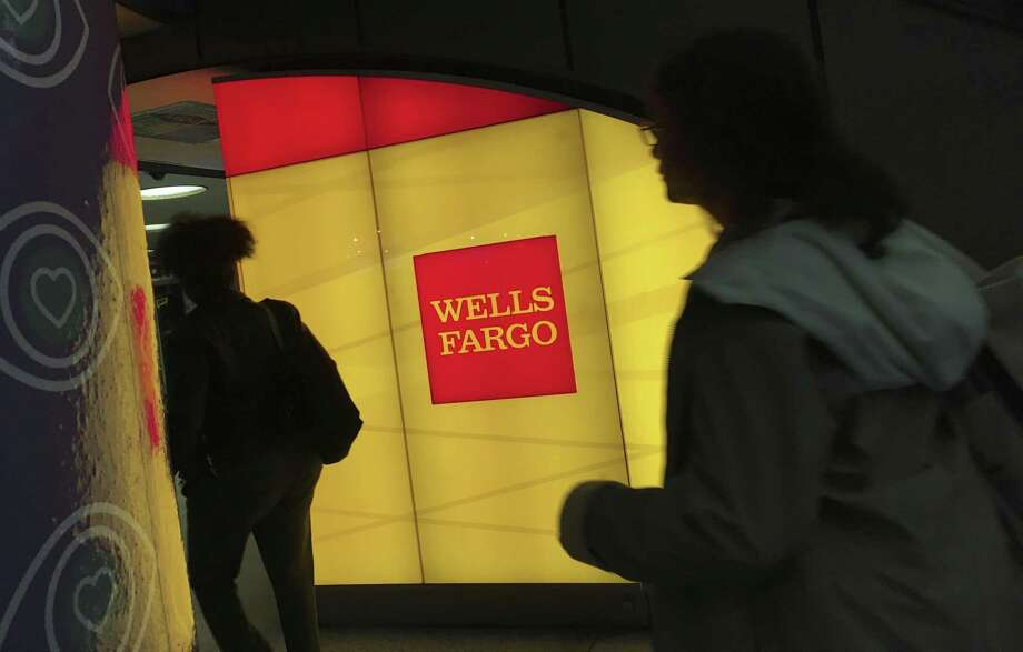 Commuters walk by a Wells Fargo ATM location at New York's Penn Station. The company took a surprise $1 billion charge in the quarter for previously disclosed regulatory investigations into its pre-crisis mortgage activity. Photo: Swayne B. Hall /Associated Press / Copyright 2017 The Associated Press. All rights reserved.