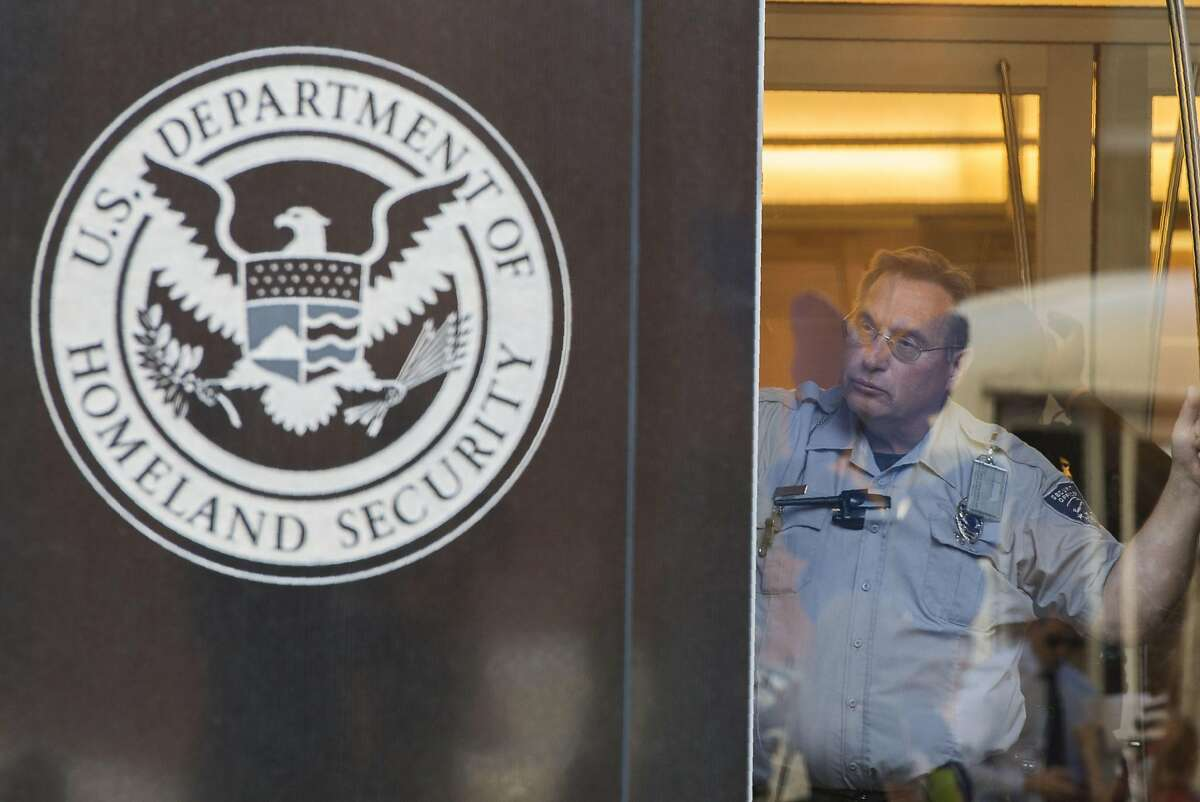 A security officer looks out of a window at the US Immigration and Customs Enforcement (ICE) office, part of the Department of Homeland Security (DHS), in Washington DC on October 4, 2017.