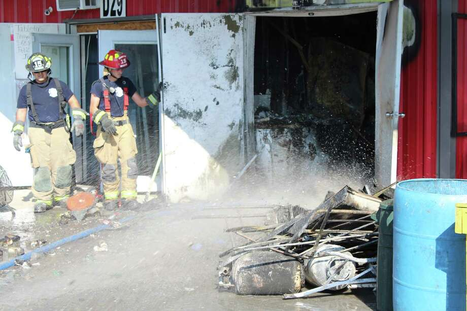 Firefighters douse hot spots at a flea market fire Friday in Cleveland. The fire originated in an area normally used for food preparation. Photo: Vanesa Brashier