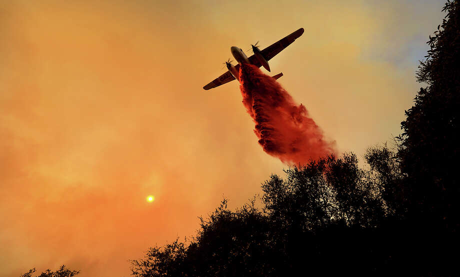 A Cal Fire air taker makes a drop on a wildfire as the pilot protects structures on the Hawkeye Ranch above Geyserville, Thursday Oct. 12, 2017. Thousands of firefighters are battling the blazes and additional manpower and equipment was pouring in from across the country and as far as Australia and Canada. (Kent Porter/The Press Democrat via AP) Photo: Kent Porter, Press Democrat Via AP