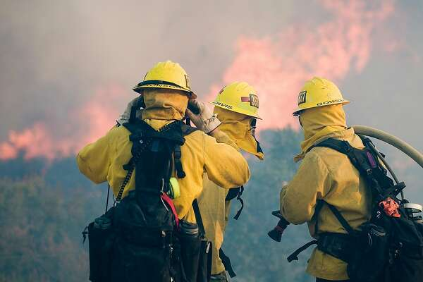 Firefighters watch flames while on structure protection of homes in Oak Hills, Calif., Friday, July 17, 2015. The fire started in the Cajon Pass along Interstate 15, the main highway between Southern California and Las Vegas and quickly chewed through bone-dry brush. (James Quigg/The Victor Valley Daily Press via AP)