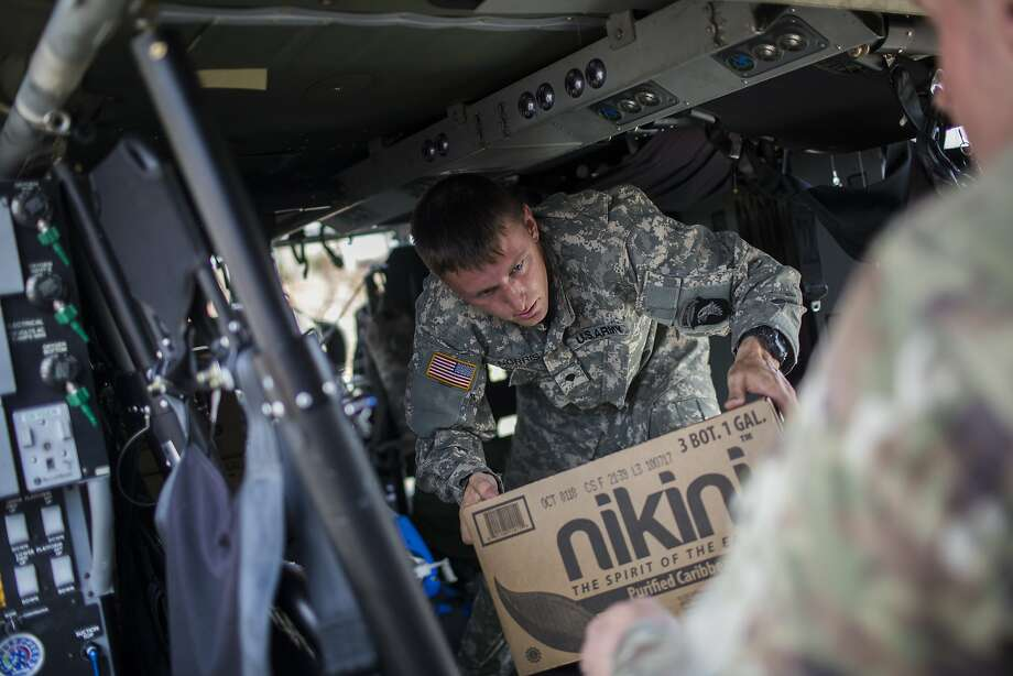 Army personnel unload helicopters carrying relief supplies in Cidra, Puerto Rico, Oct. 12, 2017. President Donald Trump suggested again on Thursday that Puerto Rico bore some of the blame for its current crisis following twin hurricanes, and that there were limits to how long he would keep troops and federal emergency workers on the island. (Dennis M. Rivera Pichardo/The New York Times) Photo: DENNIS M. RIVERA PICHARDO, NYT