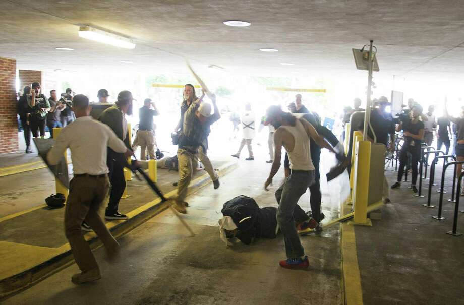 FILE - In this Saturday, Aug. 12, 2017 photo, DeAndre Harris, bottom is assaulted in a parking garage beside the Charlottesville police station after a white nationalist rally was disbursed by police, in Charlottesville, Va. Harris turned himself into police after being charged in the incident. Charlottesville police said in a statement that Harris turned himself in Thursday, Oct. 12,  and was served a warrant charging him with unlawful wounding. (Zach D. Roberts via AP) Photo: Zach D. Roberts / Associated Press / Zach D. Roberts