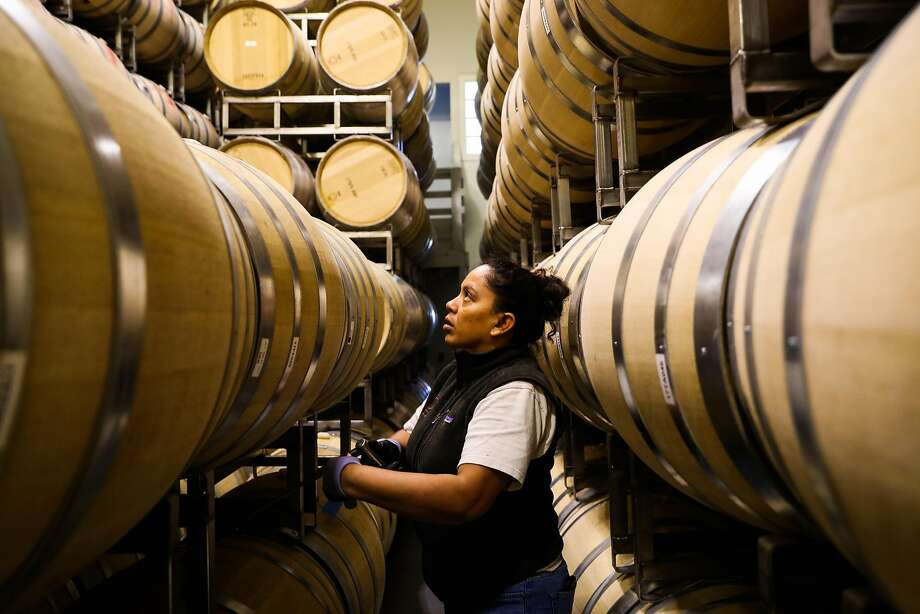Silvia Ortiz stirs a barrel of wine at Lewis Cellars in Napa. Photo: Gabrielle Lurie, The Chronicle