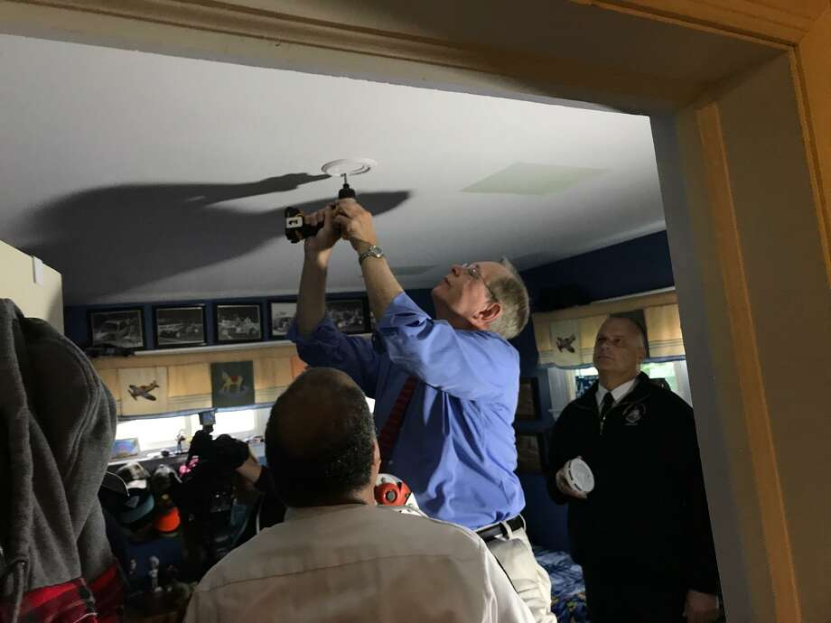 Public Safety Director Ted Jankowsky and Chief Fire Marshal Charles Spaulding (in white shirt) watching Mayor David Martin screw a smoke detector into the ceiling of a home in The Cove on Friday morning. Photo: John Nickerson / Hearst Connecticut Media