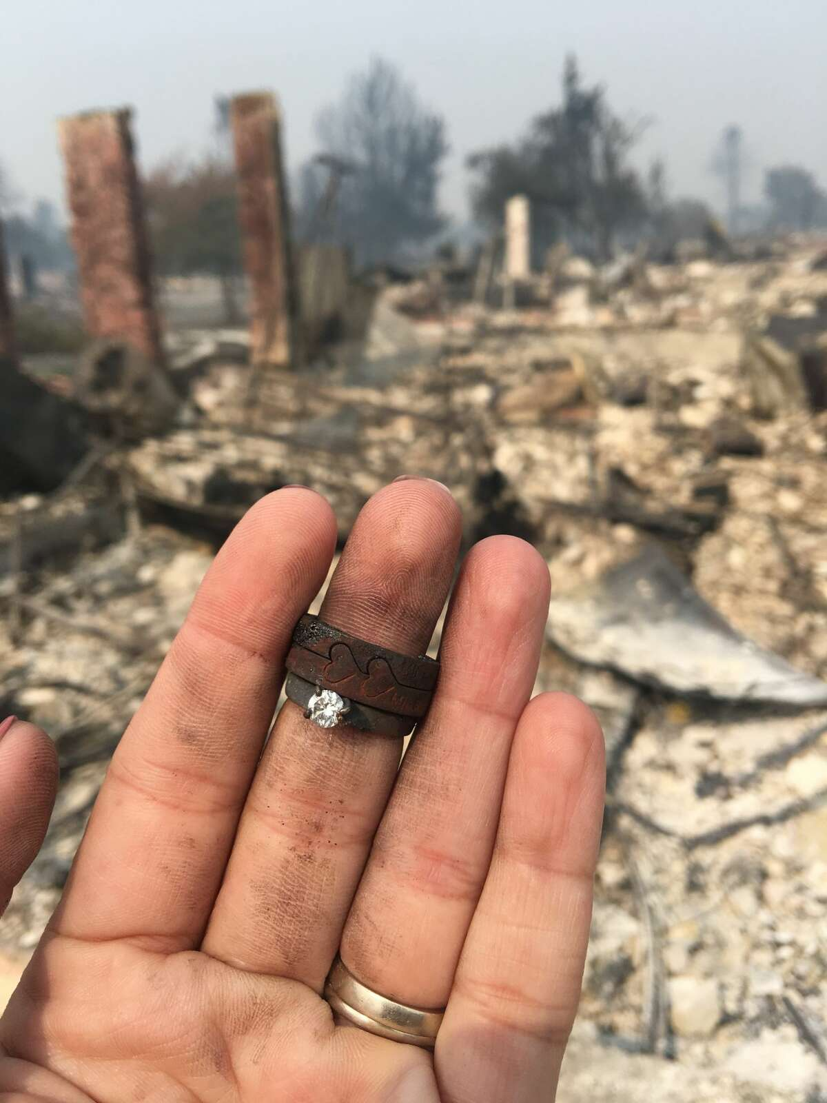 In this photo provided by Sam Brinkerhoff, his wife Monica Brinkerhoff takes a photo of her wedding ring that was found in the burned remains of her home in Santa Rosa. She had hoped to retrieve a passport from her fire-resistant safe, but that too was consumed by the flames. She wasn't prepared for what she did find, the couple's soot-covered engagement rings, with a pair of etched hearts still visible on one of the bands.