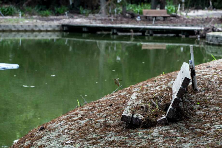 Mud and silt are piled on the banks of Story Lake, rising to the bottom of a park bench, in the aftermath of flooding from Hurricane Harvey, at Mercer Arboretum and Botanic Gardens on Thursday, Sept. 28, 2017, in Spring. Harvey devastated the gardens, washing away much of the foliage. ( Brett Coomer / Houston Chronicle ) Photo: Brett Coomer, Staff / © 2017 Houston Chronicle