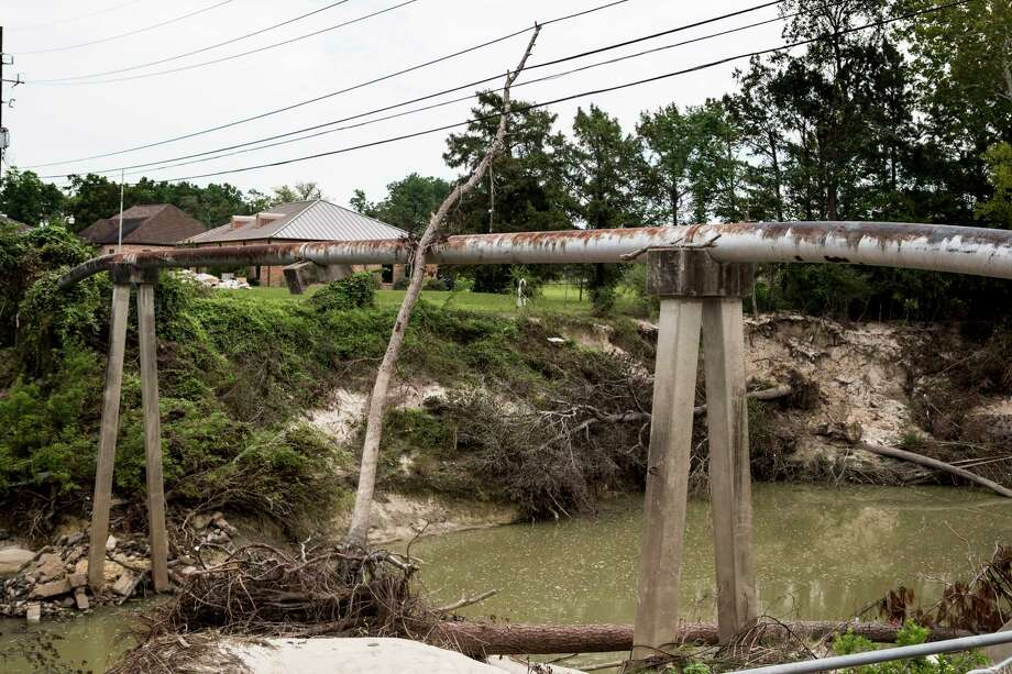 A tree is shown lodged against wires and a pipeline crossing Cypress Creek at Mercer Arboretum and Botanic Gardens on Thursday, Sept. 28, 2017, in Spring. Harvey devastated the gardens, washing away much of the foliage. ( Brett Coomer / Houston Chronicle ) Photo: Brett Coomer, Staff / © 2017 Houston Chronicle
