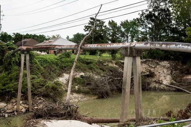 A tree is shown lodged against wires and a pipeline crossing Cypress Creek at Mercer Arboretum and Botanic Gardens on Thursday, Sept. 28, 2017, in Spring. Harvey devastated the gardens, washing away much of the foliage. ( Brett Coomer / Houston Chronicle )