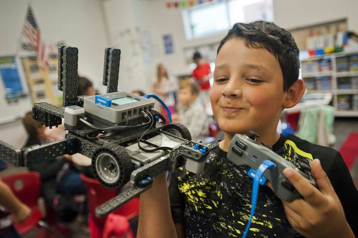 Alex Posch of Midland, 9, shows off a robot he is experimenting with along with his Central Park Elementary classmates on Friday. Donors to the school, which has a STEM focus, were able to tour the facility and observe classrooms during an open house event that took place Friday, Oct. 12, 2017. (Katy Kildee/kkildee@mdn.net)