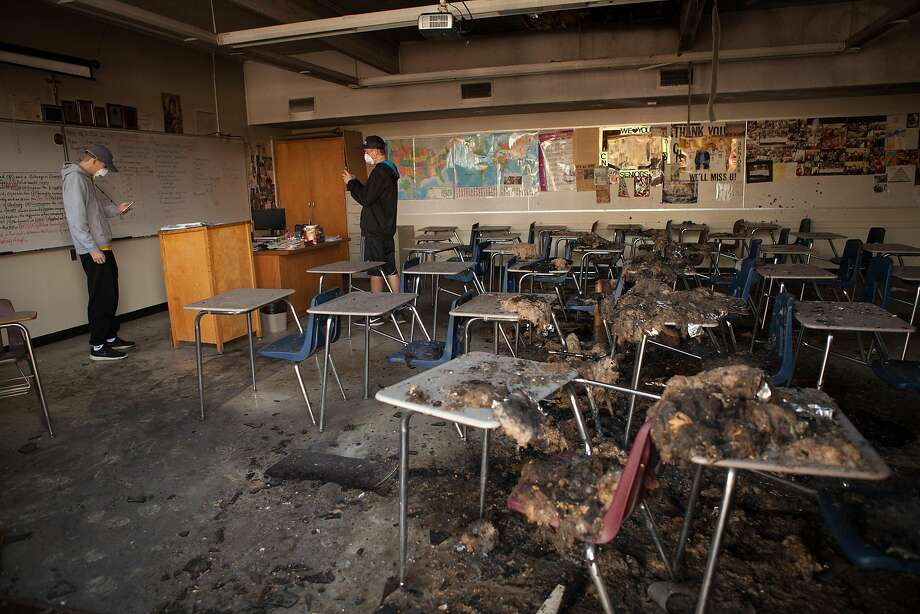 Seniors Tyler Botteri (left) and Deric Younce look through the damage inflicted on Cardinal Newman High in Santa Rosa. Photo: Alex Washburn, The Chronicle