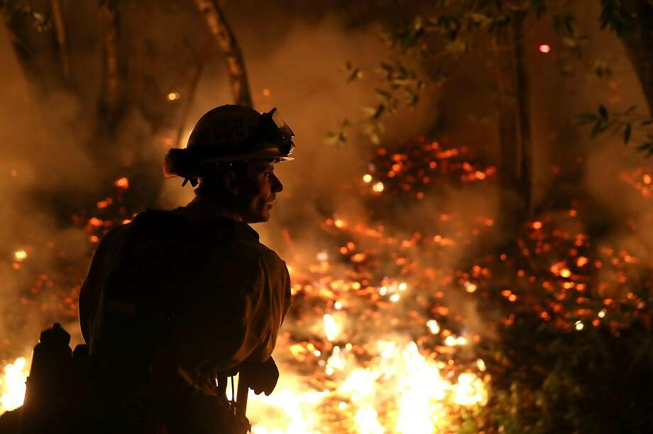 CALISTOGA, CA - OCTOBER 12:  CalFire firefighter Trevor Smith monitors a firing operation while battling the Tubbs Fire on October 12, 2017 near Calistoga, California. At least thirty one people have died in wildfires that have burned tens of thousands of acres and destroyed over 3,500 homes and businesses in several Northern California counties.  (Photo by Justin Sullivan/Getty Images) Photo: Justin Sullivan, Getty Images
