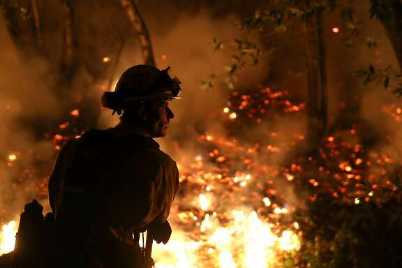 CALISTOGA, CA - OCTOBER 12:  CalFire firefighter Trevor Smith monitors a firing operation while battling the Tubbs Fire on October 12, 2017 near Calistoga, California. At least thirty one people have died in wildfires that have burned tens of thousands of acres and destroyed over 3,500 homes and businesses in several Northern California counties.  (Photo by Justin Sullivan/Getty Images)