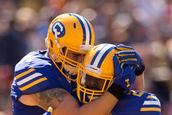 California�s Vic Enwere (23) is congratulated by teammate  Jake Curhan after scoring a touchdown against Southern California during the first quarter of an NCAA football game, on Saturday, Sept. 23, 2017 in Berkeley, Calif.