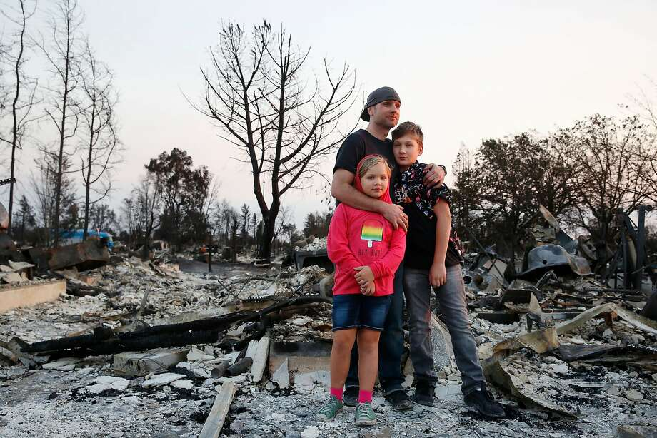 Jimmie Allen (center) stands with his children Miley Allen (left), 9, and Jaden Frank, 13, on the ashes that were their home in Coffey Park in Napa. | Photo: Lea Suzuki, The Chronicle