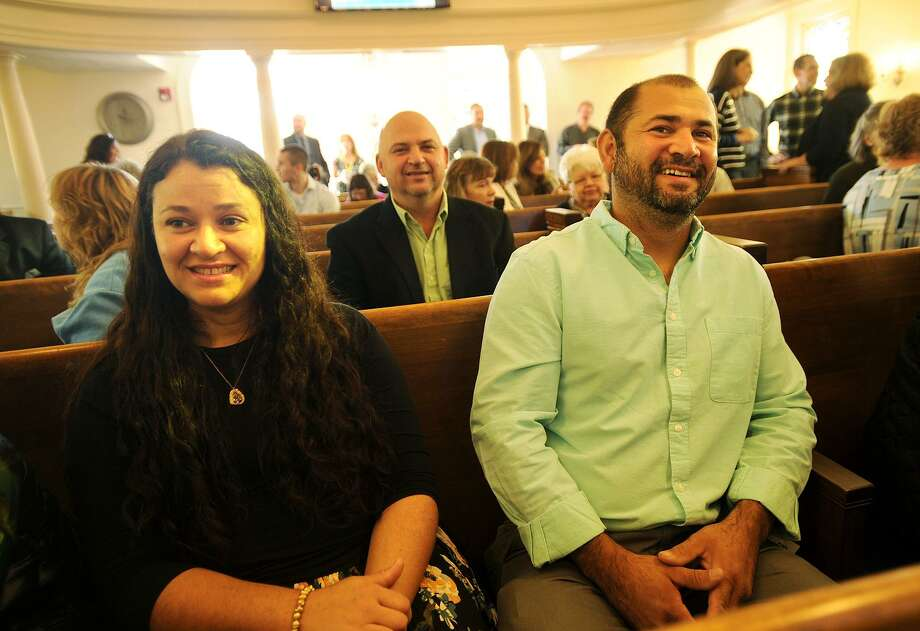 Lorena and Ricelli Fernandes, of Danbury, attend the opening service of the newly remodelled Stepney Baptist Church at 431 Main Street in Monroe, Conn. on Sunday, October 1, 2017. The pews were acquired from the former United Congregational Church in Bridgeport, which is now an Islamic mosque. Fernandes worked as the carpenter/contractor on the project. Photo: Brian A. Pounds / Hearst Connecticut Media / Connecticut Post