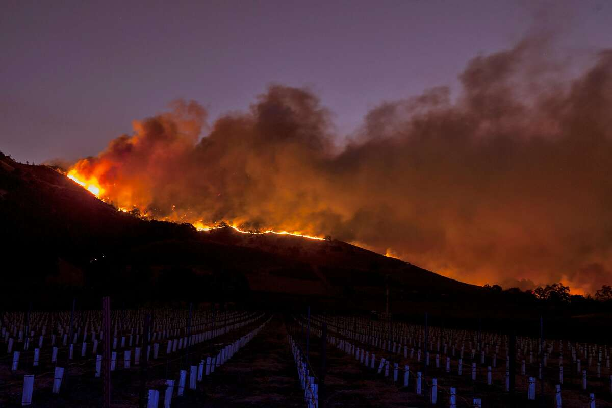 Flames moved through the hills above the Silverado Trail as a fast moving wind whipped wild fire raged though the Napa/Sonoma wine region.