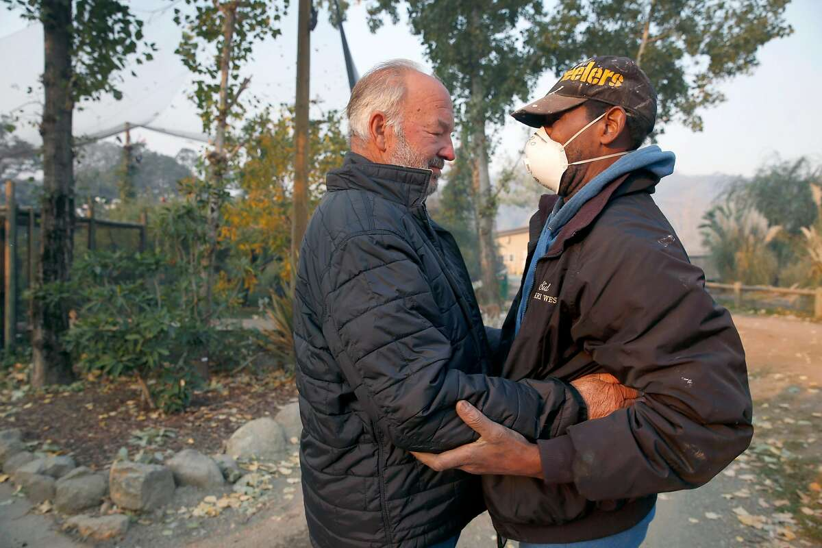 Peter Lang (left), founder and owner of Safari West, embraces maintenance employee Sid Robinson in Santa Rosa, Calif. on Friday Oct. 13, 2017. Both men lost their homes to the Tubbs Fire but not a single animal was lost and only minimal damage occurred when the firestorm raced through the wildlife preserve.