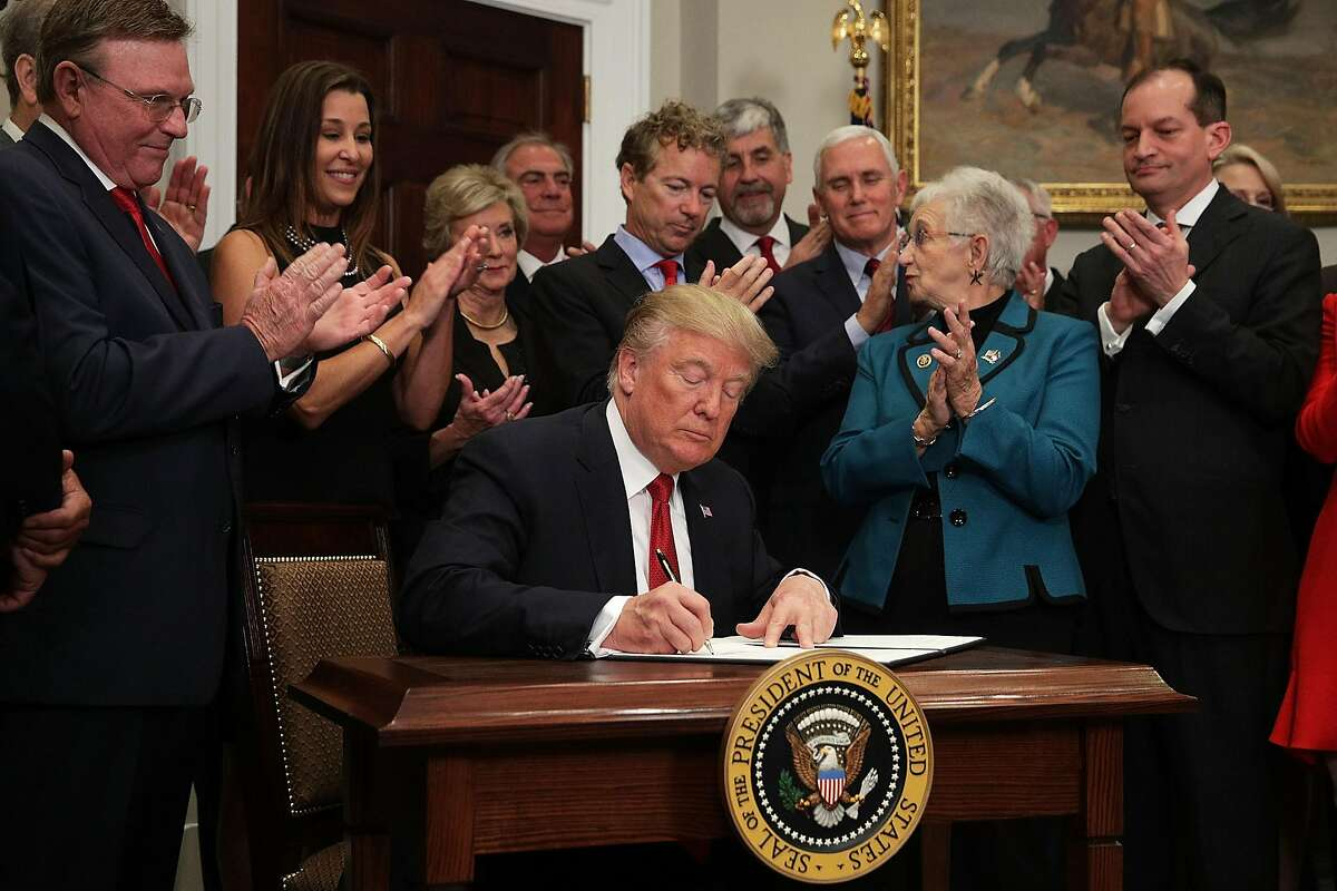 """WASHINGTON, DC - OCTOBER 12: U.S. President Donald Trump signs an executive order as Sen. Rand Paul (R-KY), Vice President Mike Pence, Rep. Virginia Foxx (R-NC) and Secretary of Labor Alexander Acosta look on during an event in the Roosevelt Room of the White House October 12, 2017 in Washington, DC. President Trump signed the executive order to loosen restrictions on Affordable Care Act """"to promote healthcare choice and competition."""" (Photo by Alex Wong/Getty Images)"""