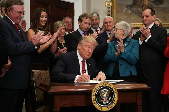 "WASHINGTON, DC - OCTOBER 12:  U.S. President Donald Trump signs an executive order as Sen. Rand Paul (R-KY), Vice President Mike Pence, Rep. Virginia Foxx (R-NC) and Secretary of Labor Alexander Acosta look on during an event in the Roosevelt Room of the White House October 12, 2017 in Washington, DC. President Trump signed the executive order to loosen restrictions on Affordable Care Act ""to promote healthcare choice and competition.""  (Photo by Alex Wong/Getty Images)"