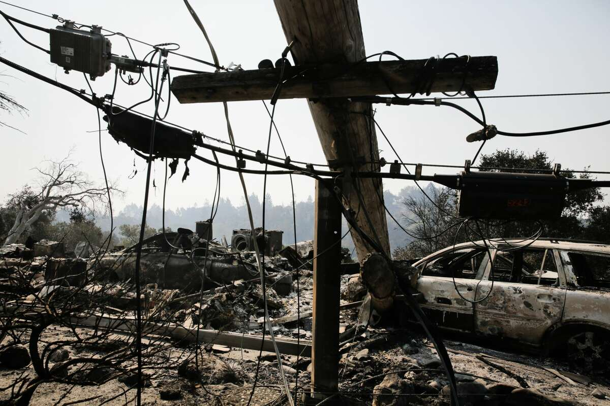 A downed power line and the remains of a home and a car are seen in the Larkfield-Wikiup neighborhood following the damage caused by the Tubbs Fire on Oct. 13, 2017 in Santa Rosa, California. Twenty four people have died in wildfires that have burned tens of thousands of acres and destroyed over 3,500 homes and businesses in several Northern California counties. (Photo by Elijah Nouvelage/Getty Images)