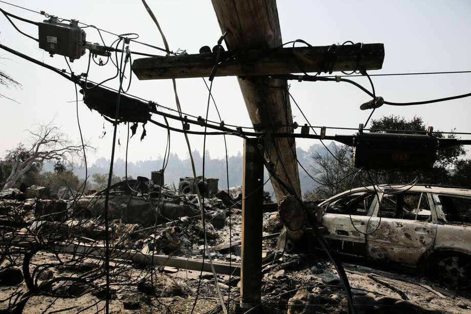 A downed power line and the remains of a home and a car are seen in the Larkfield-Wikiup neighborhood following the damage caused by the Tubbs Fire on Oct. 13, 2017 in Santa Rosa, California.  Photo: Elijah Nouvelage/Getty Images