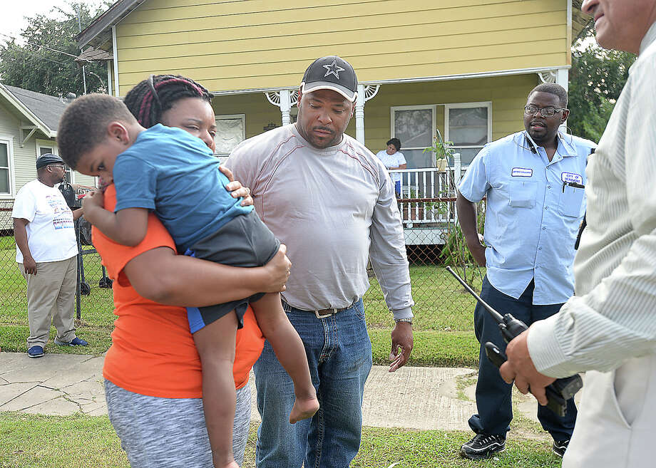 The parents of a young boy talk with police after being reunited with their missing son at a home on Avenue C in Beaumont Friday. The child was in the back of his family's SUV when it was stolen from an area residence. An AT&T service repairman working at a home nearby saw the child alone  and upset in the roadway and brought him to the house at which he was working to ask if the resident knew to whom he belonged. She started asking neighbors, including Quinton Smith, who immediately called 911. The police were nearby, as they had found the stolen vehicle a block away, and responded quickly. The suspects have not been found, and the investigation continues. Photo taken Thursday, October 12, 2017 Kim Brent/The Enterprise Photo: Kim Brent/The Enterprise