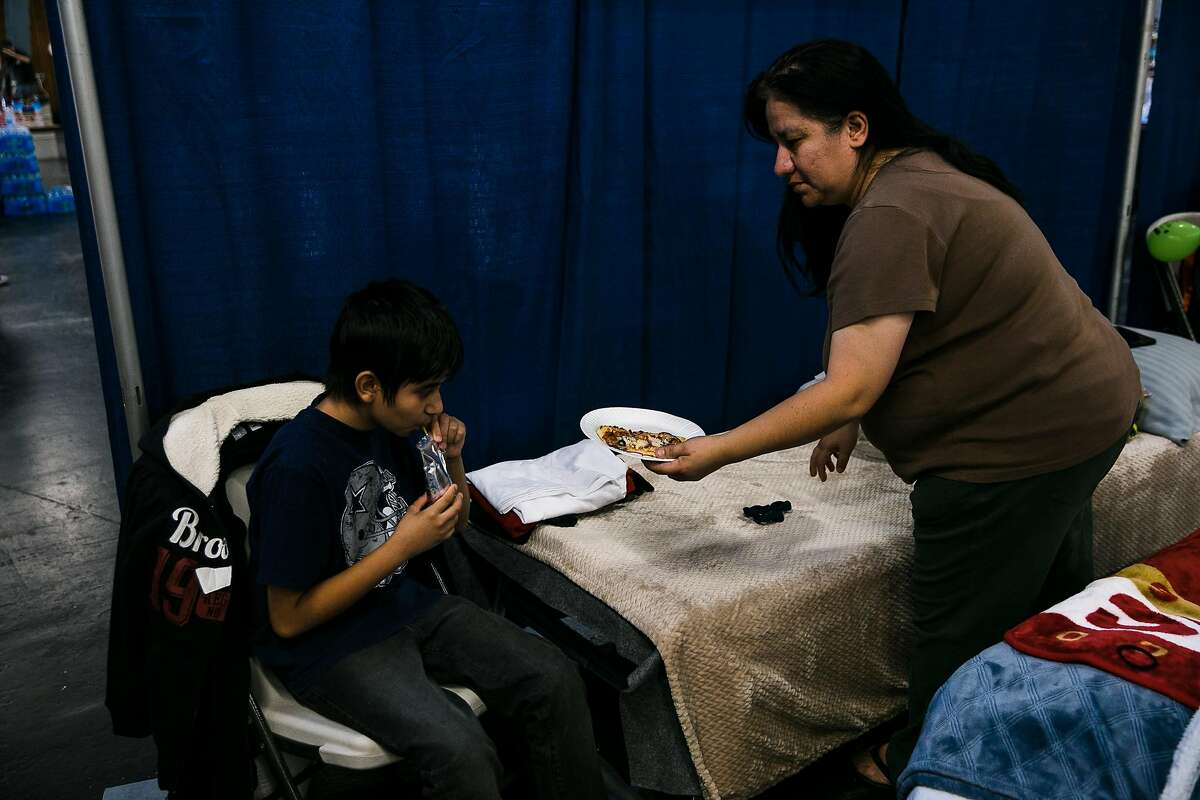Imelda Flores hands lunch to James Flores, 12 at Sonoma County Fairgrounds Shelter in Santa Rosa, Calif. Friday, October 13, 2017. The Flores are waiting for electricity to return to their house.