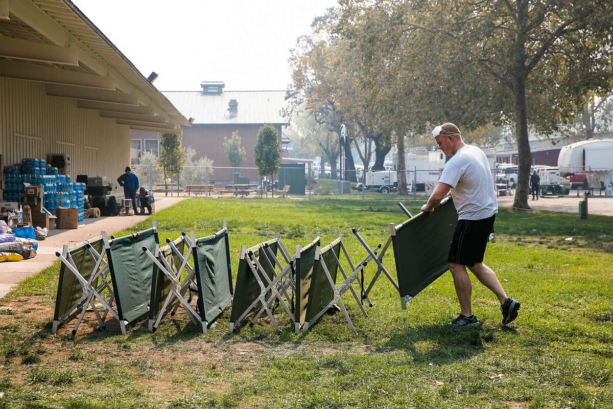 Paul Savage of Santa Rosa lines the cots outside for cleaning at Sonoma County Fairgrounds Shelter in Santa Rosa, Calif. Friday, October 13, 2017.