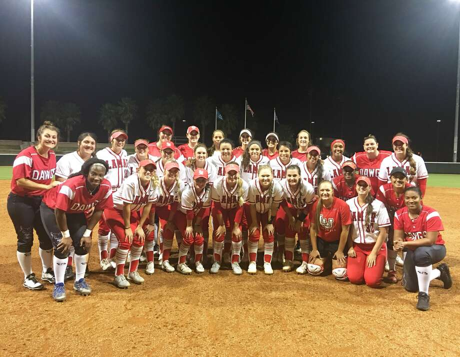 The Lamar Cardinals softball team posed for a photo with members of the National Pro Fast Pitch League team, the Scrap Yard Dawgs. (@LamarSoftball)