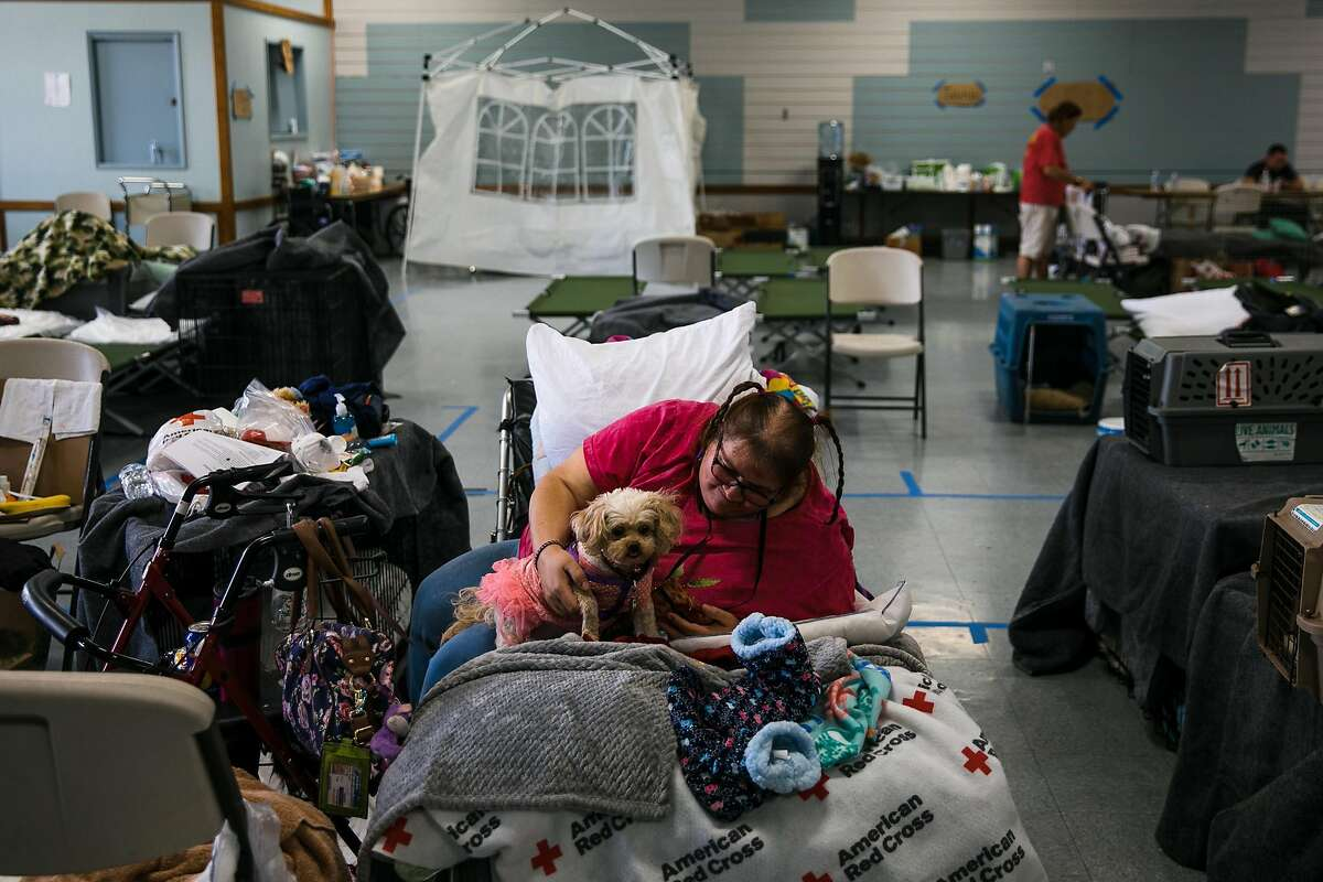 Cybrena Gunn of Santa Rosa comforts her dog, Princess Honey Girl at the Sonoma County Fairgrounds Shelter in Santa Rosa, Calif. Friday, October 13, 2017. Gunn is waiting to return to home when the power and water return.