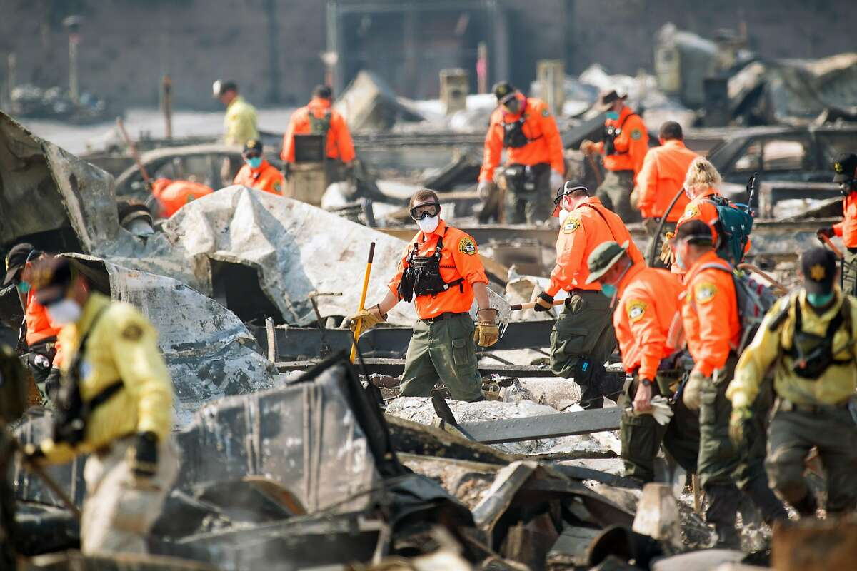 Search and rescue workers comb through the Journey's End Mobile Home Park on Friday, Oct. 13, 2017, in Santa Rosa, Calif. According Sgt. Dave Thompson, in charge of search and rescue operations for the Sonoma County Sheriffs Office, crews have recovered another body at the site.
