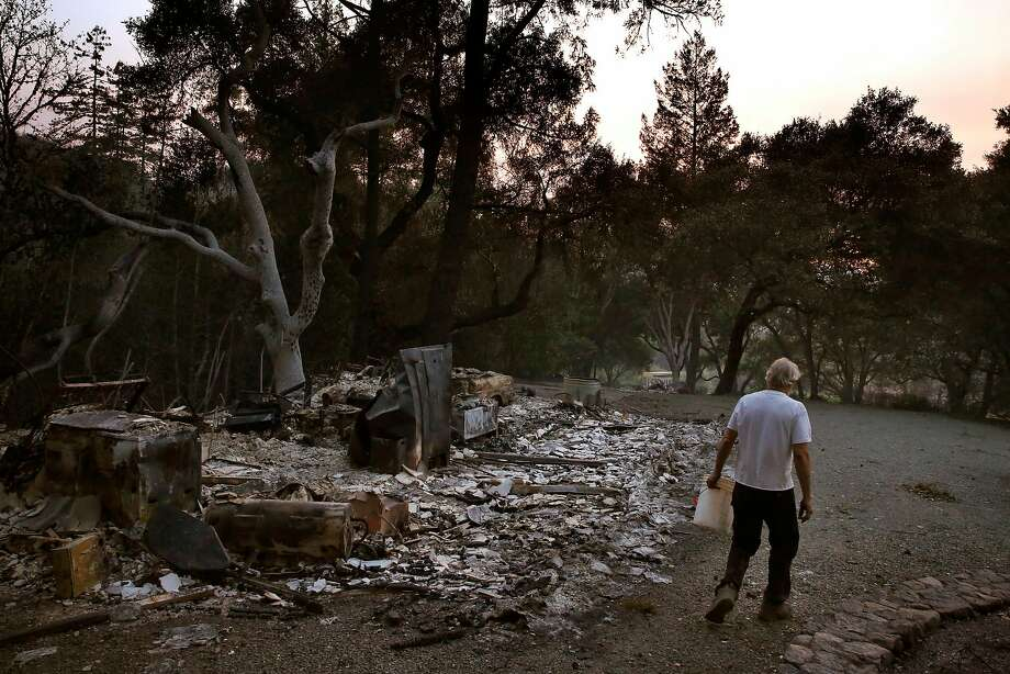 Richard Horwath walks back to his tractor after putting out a hot spot on his neighbor's property in Calistoga on Thursday. The Horwaths bought the property 30 years ago, but they finished building their new home in 2010. Though most of their neighbors' homes were destroyed, the Horwaths' home survived the fire. Photo: Leah Millis, The Chronicle