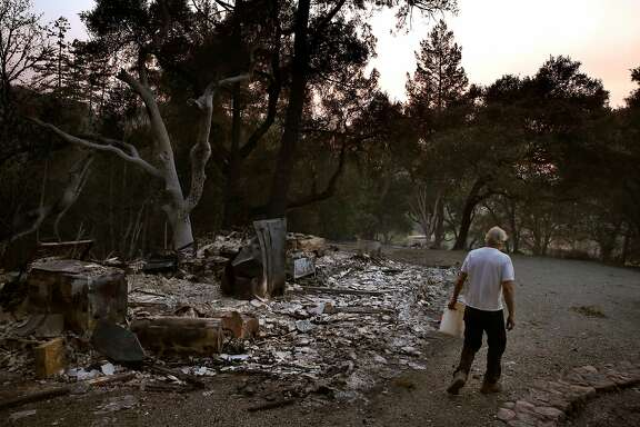 """Richard Horwath walks back to his tractor after putting out a hot spot on his neighbor's property Oct. 12, 2017 in Calistoga, Calif. The Horwath's bought the property 30 years ago, but they only finished building their new home in 2010. Richard Horwath got up to go to bed when first smelled smoke in their bedroom, he then ran outside and saw the sky was orange. The power went out right after Richard grabbed his firehose that could have pumped hundreds of gallons of water a minute and that was when he and Kathy decided they needed to go. Neighbors were driving up and down the road outside, frantically honking their horns and the wind was blowing hard in their direction. After pausing to close every window so as to keep embers out, the Horwath's left. As they began driving down the road, they started to hear """"monstrous explosions"""" of nearby houses going up in flames. As the fire crested the ridge above their home, Richard said it sounded like a freight train. The two of them white-knuckle drove the whole way out towards Healdsburg, at one point having to drive through a vineyard to avoid downed trees. On highway 101, trees were falling left and right from the wind. An hour after they left, when they were heading down 101 past Santa Rosa, they could already see the fire making its way down Mark West Springs Rd towards the city. Though most of their neighbors homes were destroyed, their home made it."""
