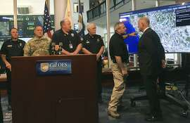 Gov. Jerry Brown, far right, is briefed on wildfires burning across California by Mark Ghilarducci, pointing to map, director of the Governor's Office of Emergency Services, before a media briefing at the Cal OES headquarters near Sacramento, on Wednesday, Oct. 11, 2017. Gov. Brown warns that catastrophic wildfires will keep ripping through the state as the climate warms. Brown told reporters Wednesday that more people are living in communities close to forests and brush that easily ignite because of dry weather. (AP Photo/Donald Thompson)