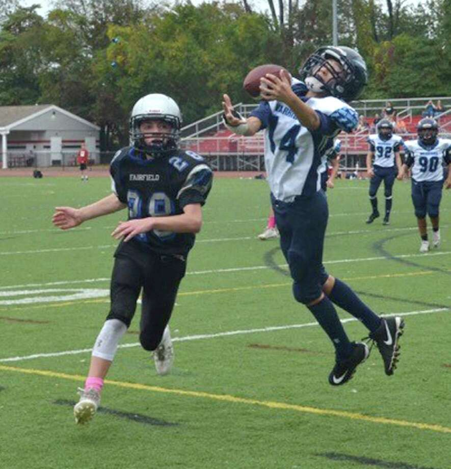 Cornerback Ryan Preisano, right, makes a one-handed catch to halt a Fairfield drive by intercepting the pass in the end zone during youth football action last week. Photo: Contributed Photo / Hearst Connecticut Media / Norwalk Hour