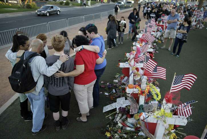 People pray Oct. 9 at a makeshift memorial for victims of the mass shooting in Las Vegas. Gunman Stephen Paddock opened fire Oct. 1 from a room at the Mandalay Bay resort and casino, on an outdoor country music concert, killing dozens and injuring hundreds. Times like these should not be politicized.