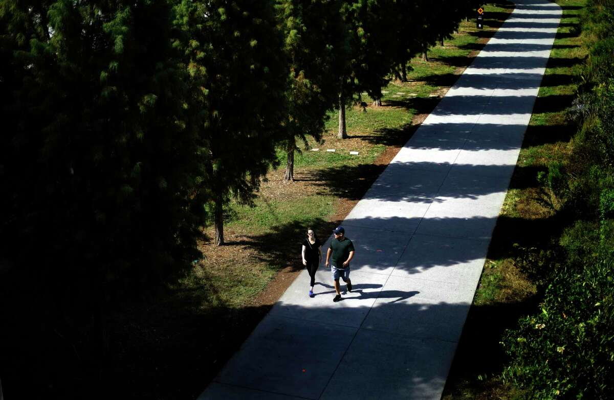 Pedestrians walk along the BeltLine trail in Atlanta, Friday, Oct. 13, 2017. Summer-like temperatures in the low eighties are expected to remain in the metro area through the weekend. (AP Photo/David Goldman)