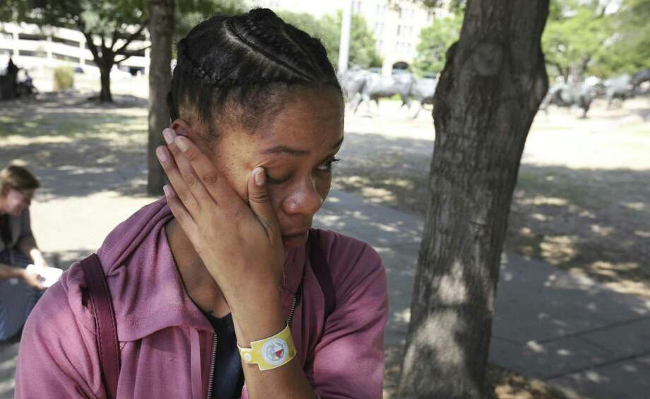 Harvey evacuee Paige Cane wipes way tears during a visit to Pioneer Plaza in downtown Dallas in September. Cane evacuated with her family from Port Arthur during flooding. A neighbor was the first to tell Cane that her landlord had posted an eviction notice on the door of her flooded apartment. Photo: LM Otero /Associated Press / Copyright 2017 The Associated Press. All rights reserved.