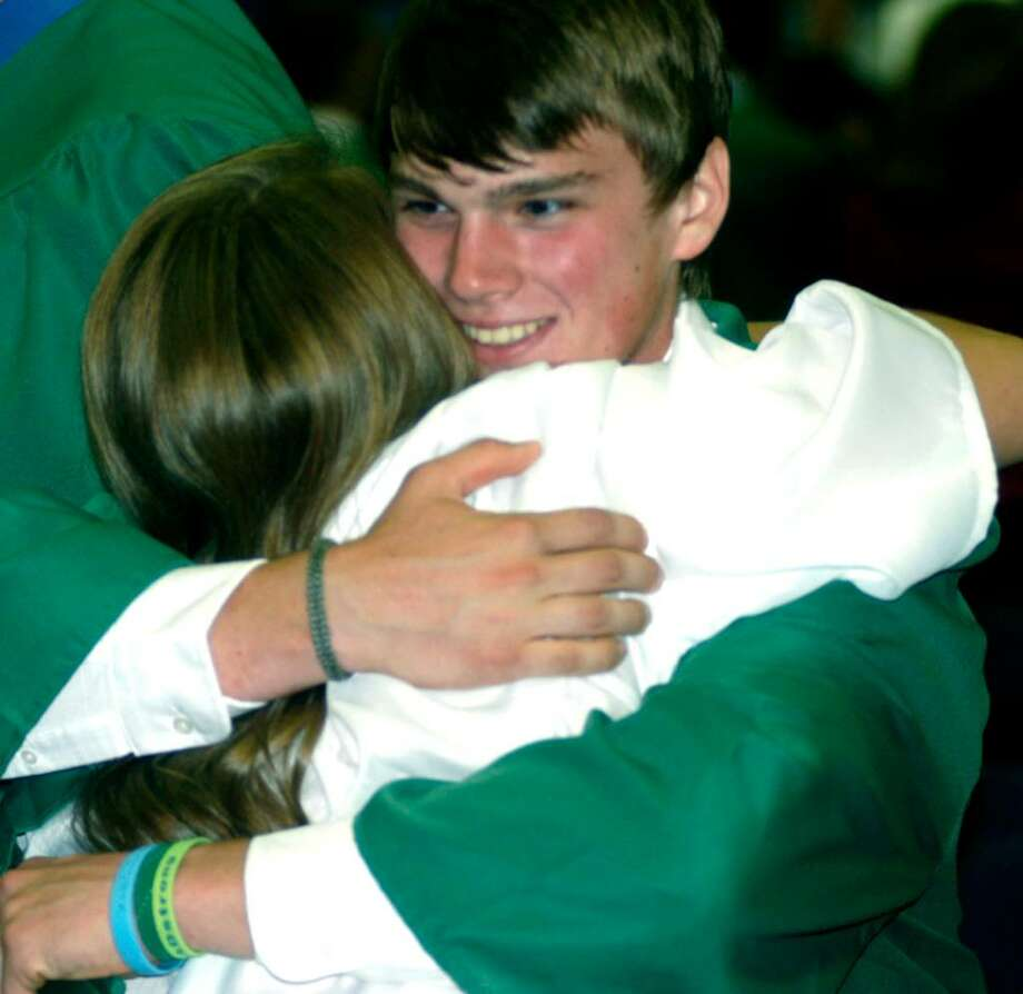 SPECTRUM/Sean McMahon hugs fellow graduate Brittany Klein after the June 19, 2010 New Milford High School commencement exercises at the O'Neil Center at Western Connecticut State University in Danbury. Photo: Norm Cummings / The News-Times