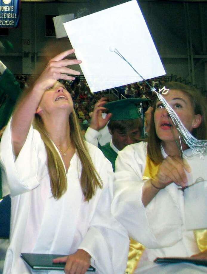 SPECTRUM/Graduate Olivia Taylor flips her hat in the air as Ellie Lamb prepares to do likewise at the June 19, 2010 New Milford High School commencement exercises at the O'Neil Center at Western Connecticut State University in Danbury. Photo: Norm Cummings / The News-Times