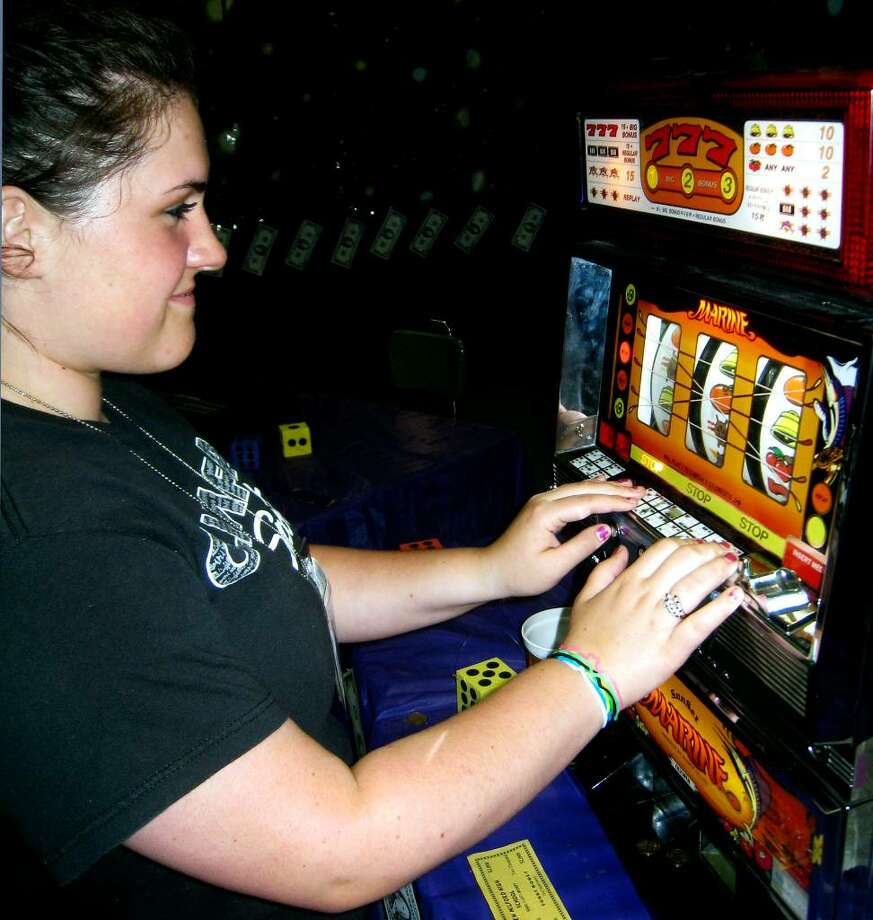 SPECTRUM/Karly Gallagher tests her fortune at the slot machine during the June 19, 2010 New Milford High School grad party. Photo: Norm Cummings / The News-Times