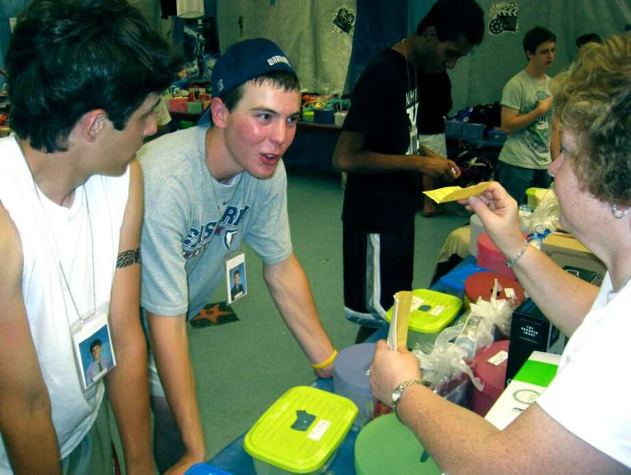 "SPECTRUM/Joe Crisalli, left, and Gavin Lavallee talk ""business"" with grad party volunteer while deciding what prizes to cash in for at the June 19, 2010 New Milford High School grad party. Photo: Norm Cummings / The News-Times"